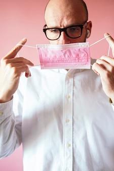Mann mit brille, die rosa maske aufsetzt