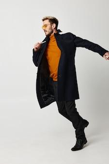 Mann mit brille mode frisur schwarzer mantel bewegung tanz