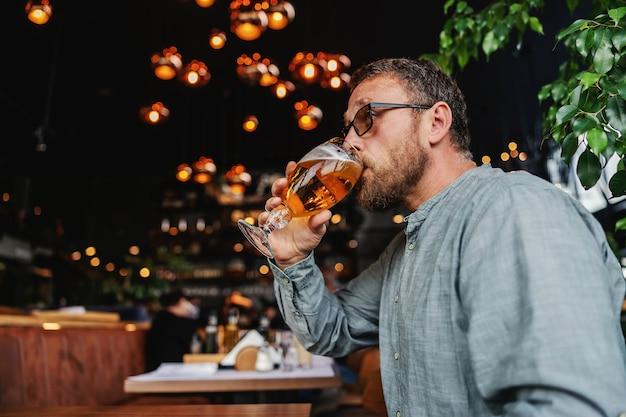 Mann mit brille sitzt in einer bar und trinkt nach der arbeit ein glas frisches kaltes helles bier.