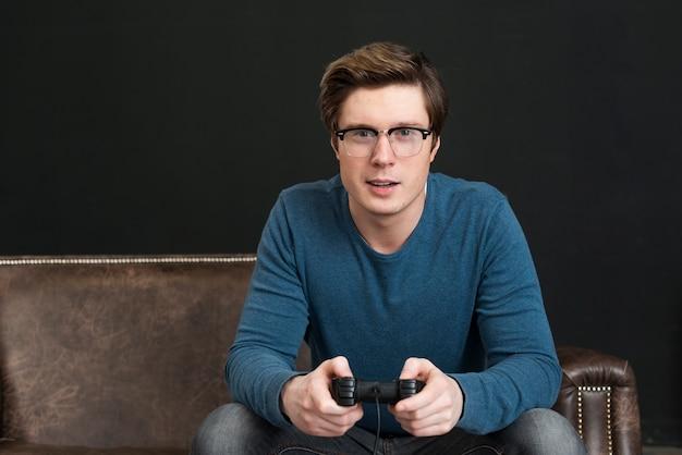 Mann mit brille spielt mit einem controller