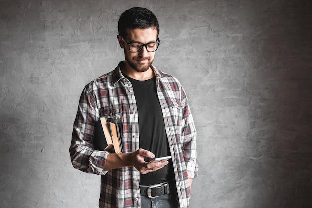 Mann mit büchern und blick auf den bildschirm eines smartphones. konzept der bildung