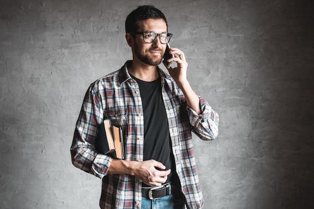 Mann mit büchern und blick auf den bildschirm eines smartphones.