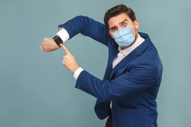 Mann mit chirurgischer medizinischer maske, der die zeit auf seiner uhr anzeigt