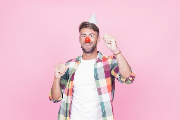 Mann mit clownnasentanzen auf rosa hintergrund