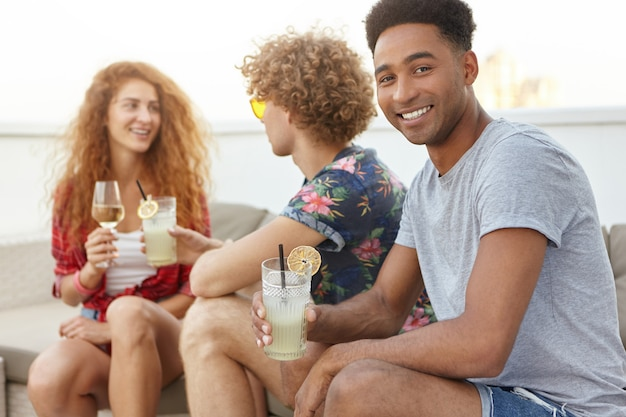 Mann mit cocktail, der kamera betrachtet und lächelt