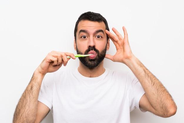 Mann mit dem bart, der die zähne putzt, die überraschungsgeste bilden