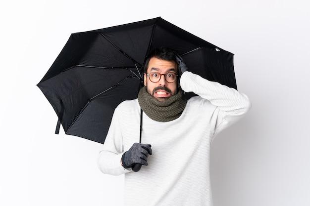 Mann mit dem bart, der regenschirm über lokalisierter wand hält