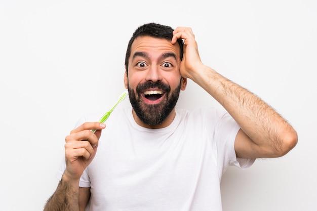 Mann mit dem bart, der zähne über lokalisiertem weiß putzt, überraschungsgeste machend