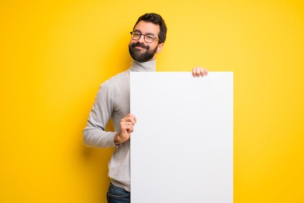Mann mit dem bart und rollkragenpullover, die ein leeres plakat für einfügen ein konzept halten