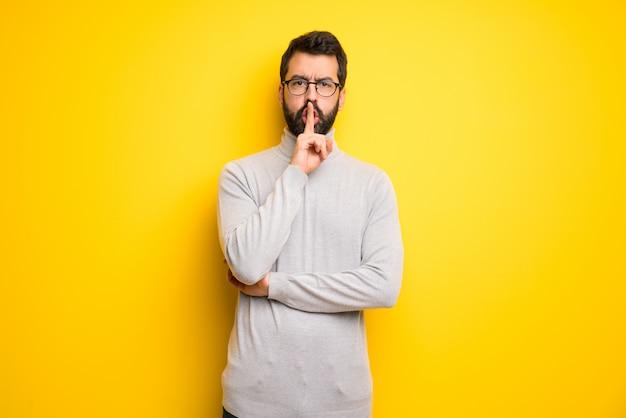 Mann mit dem bart und rollkragenpullover, die ein zeichen der ruhegeste zeigt, die finger in mund setzt