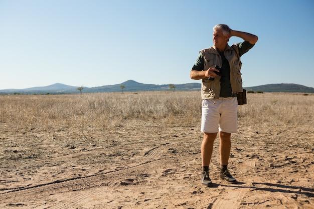 Mann mit dem binokularen schauen weg bei der stellung auf landschaft