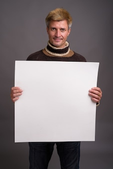 Mann mit dem blonden haar, das rollkragenpullover trägt, lokalisiert gegen graue wand