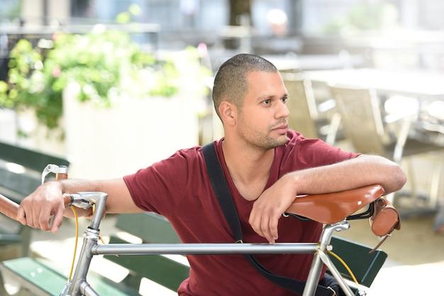 Mann mit dem fahrrad, das auf parkbank sitzt