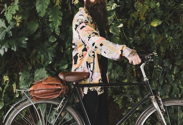 Mann mit dem fahrrad, das vor blättern steht