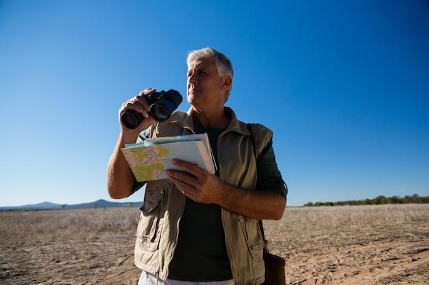 Mann mit dem fernglas und karte, die auf landschaft stehen