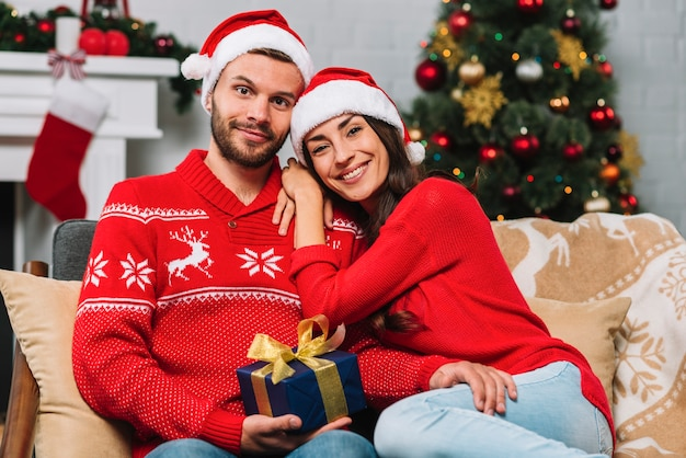 Mann mit dem geschenk, das nahe glücklicher frau sitzt
