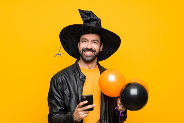 Mann mit dem hexenhut, der die schwarzen und orange luftballone für halloween-partei sendet eine mitteilung mit dem mobile hält