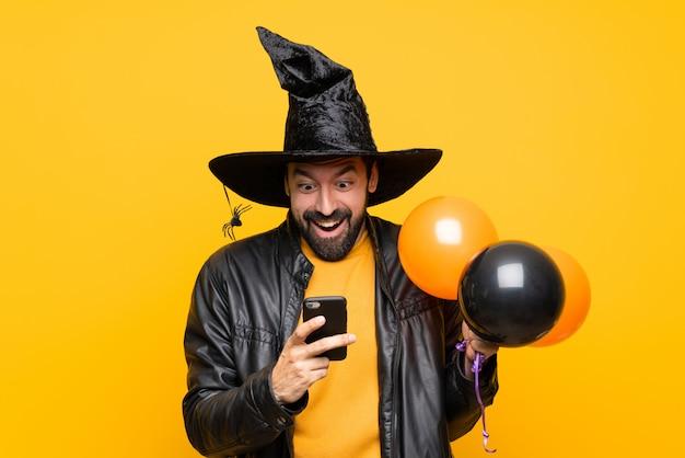 Mann mit dem hexenhut, der die schwarzen und orange luftballone für halloween-partei überrascht hält und eine mitteilung sendet