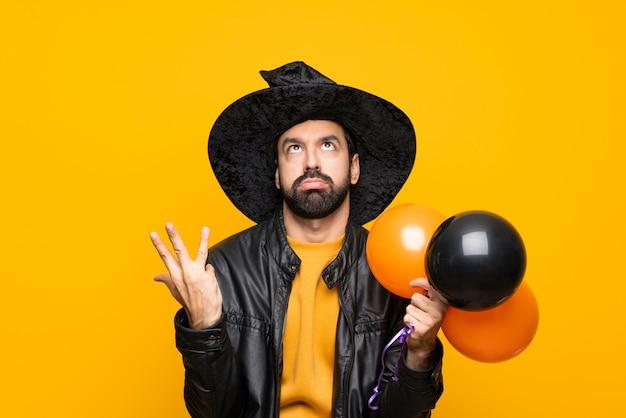 Mann mit dem hexenhut, der die schwarzen und orange luftballone für halloween-party frustriert durch eine schlechte situation hält