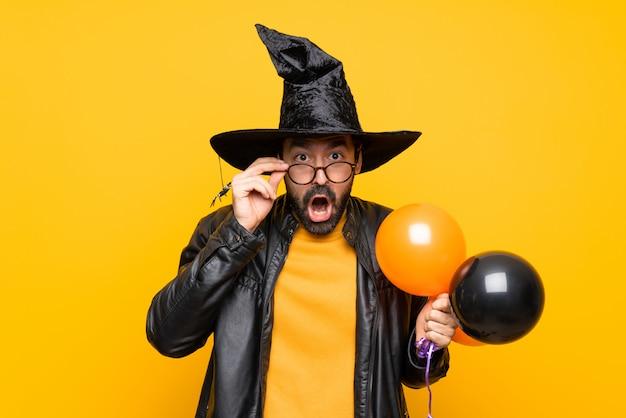 Mann mit dem hexenhut, der die schwarzen und orange luftballone für halloween-party mit gläsern und überrascht hält