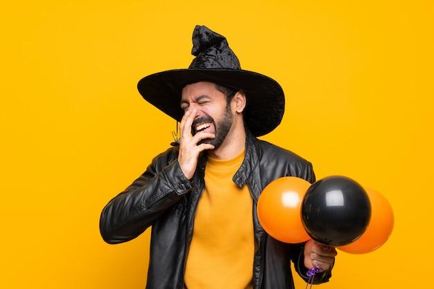 Mann mit dem hexenhut, der die schwarzen und orange luftballone für halloween-party viel lächelnd hält