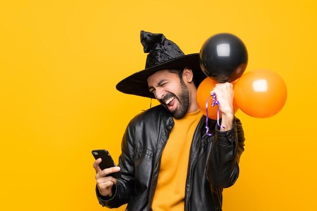 Mann mit dem hexenhut, der schwarze und orange luftballone für halloween-partei mit telefon in siegposition hält