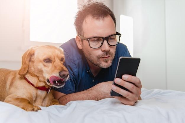 Mann mit dem hund, der intelligentes telefon auf dem bett verwendet