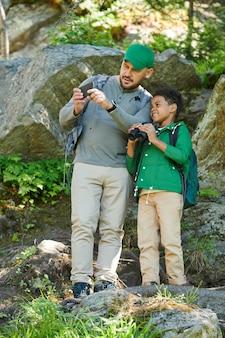 Mann mit dem jungen, der auf den felsen steht und bild der schönen natur auf handy macht