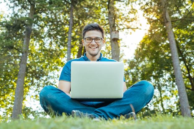 Mann mit dem laptop, der draußen in der natur sitzt