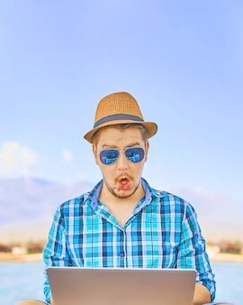 Mann mit dem laptop, der entfernt am bunten strand von insel arbeitet