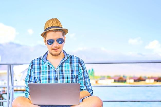 Mann mit dem laptop, der entfernt auf buntem strand von insel, auf den piers läuft.