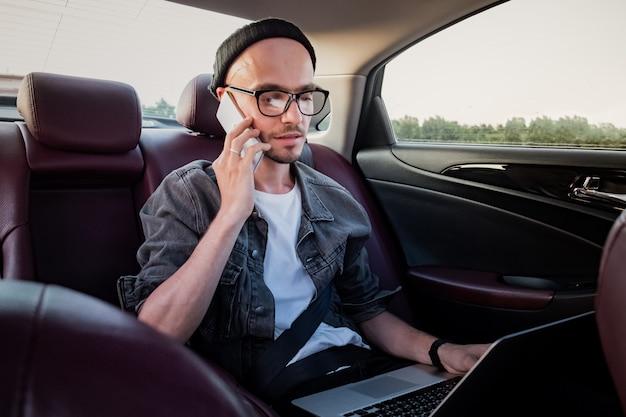Mann mit dem laptop, der telefonanruf auf einem rücksitz eines autos auf reise zur arbeit macht.