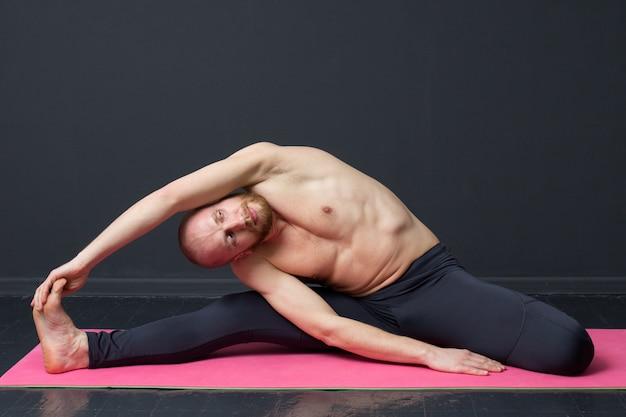 Mann mit dem nackten torso tut neigung zu den zehen