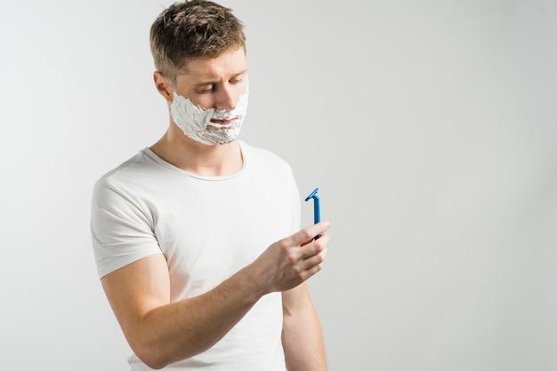 Mann mit dem rasieren des schaums auf seinem gesicht, welches das blaue rasiermesser steht gegen grauen hintergrund betrachtet