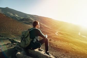 Mann mit dem Rucksack, der auf Felsen bei Sonnenuntergang auf Vulkan Ätna-Berg in Sizilien sitzt