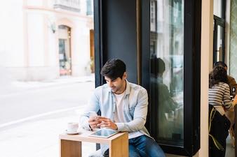 Mann mit dem Smartphone, der im Café sitzt