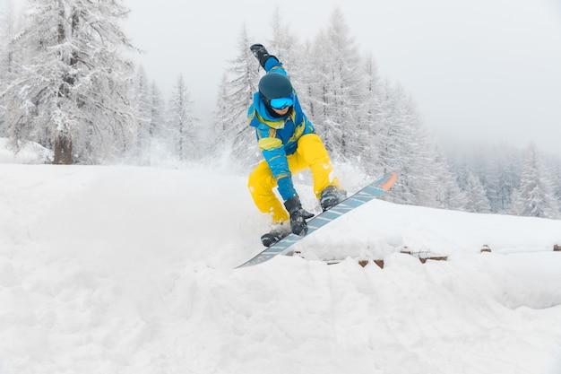 Mann mit dem snowboard, der tricks auf dem schnee springt und tut