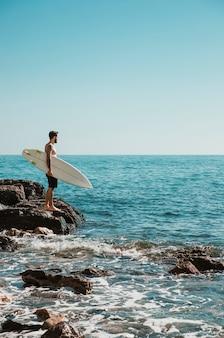 Mann mit dem surfbrett, das auf steinigem ufer steht