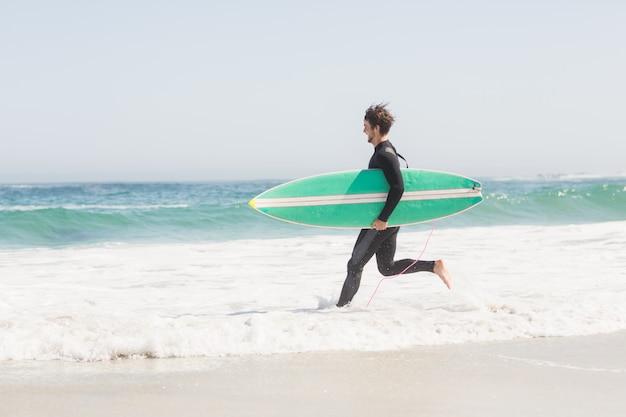 Mann mit dem surfbrett, das in richtung zum meer läuft