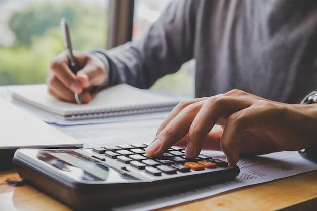 Mann mit dem taschenrechner, der zählt, anmerkungen an der bürohand machend, schreibt in ein notizbuch