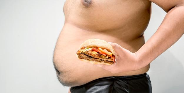 Mann mit dem überladenen bauch, der hamburger auf seiner hand hält