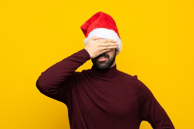 Mann mit dem weihnachtshut, der seine augen über getrenntem gelbem hintergrund abdeckt