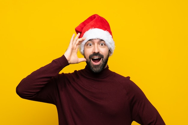 Mann mit dem weihnachtshut, der überraschungsgeste über lokalisiertem gelbem hintergrund tut