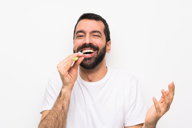 Mann mit den bürstenden zähnen des bartes über getrenntem weiß