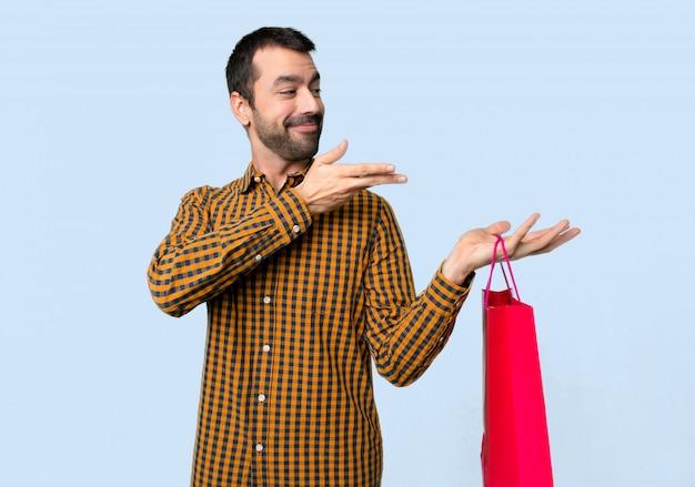 Mann mit den einkaufstaschen, die hände zur seite ausdehnen, damit die einladung auf lokalisierten blauen hintergrund kommt