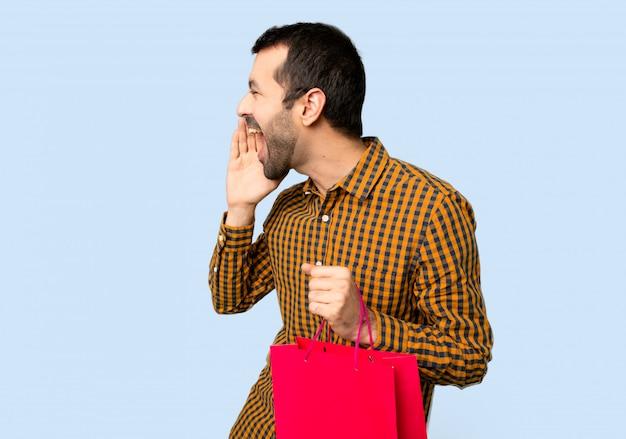 Mann mit den einkaufstaschen, die mit dem breiten mund schreien, öffnen sich zum seitlichen auf lokalisiertem blauem hintergrund