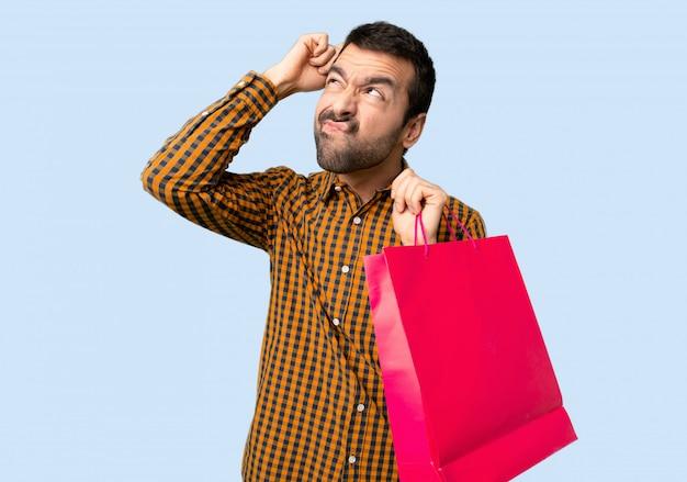 Mann mit den einkaufstaschen, die zweifel beim verkratzen des kopfes auf lokalisiertem blauem hintergrund haben