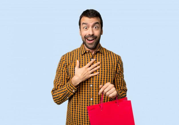 Mann mit den einkaufstaschen überrascht und beim schauen auf lokalisiertem blauem hintergrund recht geschockt