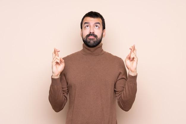 Mann mit den fingern, die das beste kreuzen und wünschen