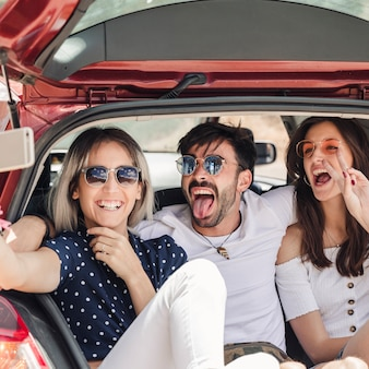 Mann mit den freundinnen, die im auto-lkw aufwirft für selbstporträt sitzen